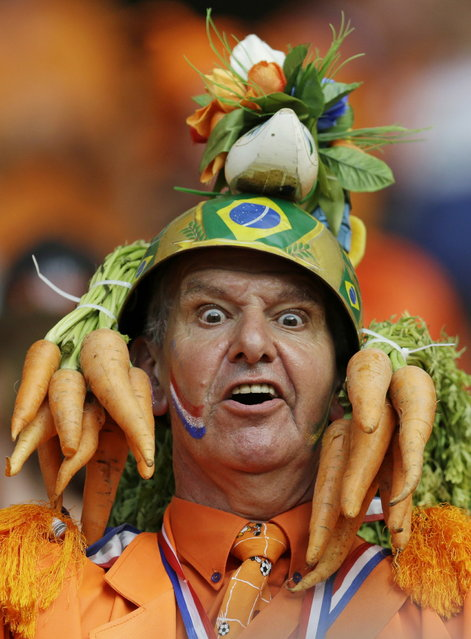 In this Friday, June 13, 2014 photo, a Dutch fan wears a homemade hat during the group B World Cup soccer match between Spain and the Netherlands at the Arena Ponte Nova in Salvador, Brazil. A dominating second half had the orange-clad Dutch fans in Arena Fonte Nova on their feet as they watched their team thrash the world champions 5-1. It was the worst loss for Spain in the game's showcase tournament since a 6-1 defeat to Brazil in 1950. (Photo by Natacha Pisarenko/AP Photo)