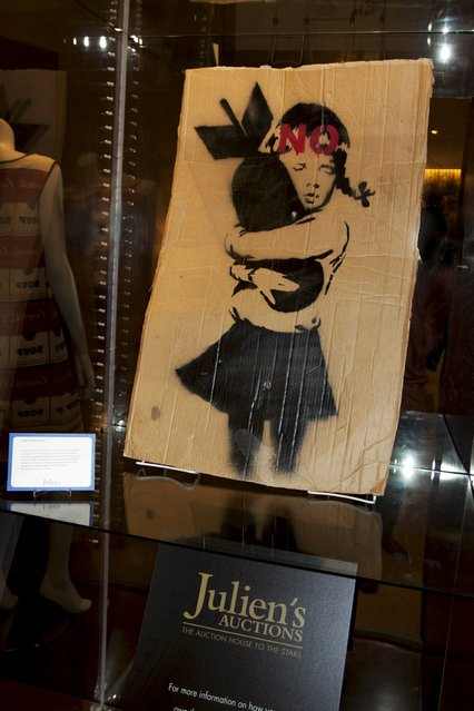 "A painting entitled ""Bomb Hugger"" is shown on display in a hotel in Beverly Hills, California in this June 28, 2015 handout photo released to Reuters July 28, 2015. ""Bomb Hugger"" and a huge street mural painted on a derelict Detroit auto factory by elusive British artist Banksy is going up for auction in Beverly Hills and could fetch up to $400,000 dollars for a local  non-profit group, Julien's Auctions said on Wednesday. (Photo by Reuters/Julien's Auctions)"