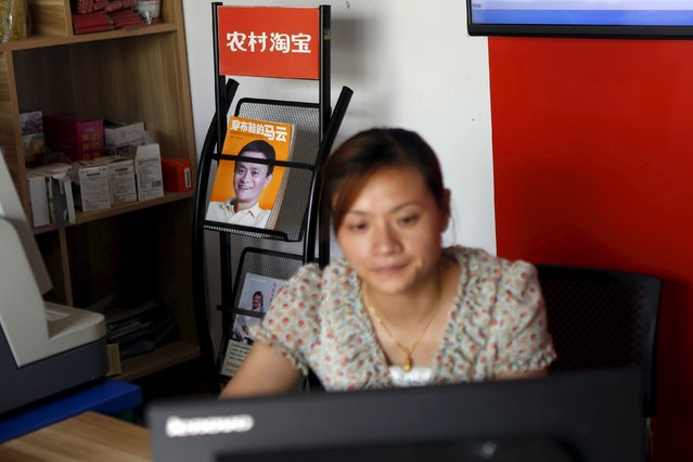 Zheng Liying looks at a computer screen in front of a picture of Alibaba founder Jack Ma, seen on the cover of a publication, at Zheng's Alibaba rural service centre in Jinjia Village, Tonglu, Zhejiang province, China, July 20, 2015. E-commerce growth in the countryside now outpaces that in major cities, though fewer than one tenth of online purchases made on Alibaba platforms were shipped to rural areas in the first quarter of this year. Alibaba estimates the potential market at 460 billion yuan ($74 billion) by next year. (Photo by Aly Song/Reuters)