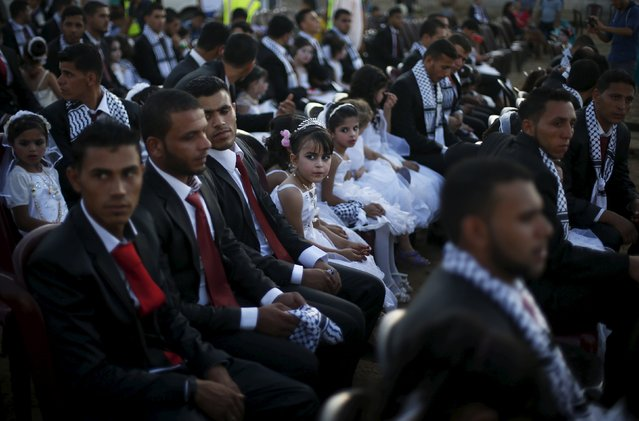 Girls accompany grooms as they sit separate from the brides during a mass wedding for 150 couples in Beit Lahiya town in the northern Gaza Strip July 20, 2015. (Photo by Suhaib Salem/Reuters)