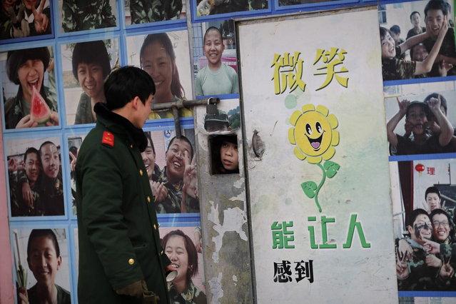 A teacher talks to an instructor who is an ex-soldier through a window in a door while pupils take part in military-style close-order drill class at the Qide Education Center in Beijing February 19, 2014. (Photo by Kim Kyung-Hoon/Reuters)