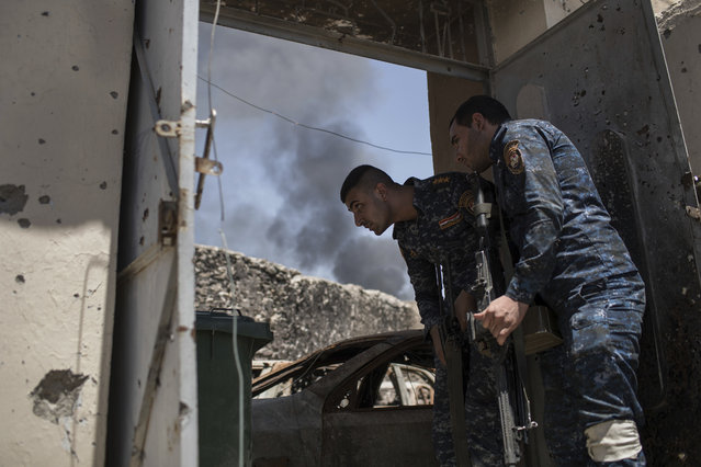 Federal policemen watch Islamic State positions at the frontline during fighting in the Old City of Mosul, Iraq, Monday, June 26, 2017. Islamic State fighters launched a string of counterattacks in a western Mosul neighborhood that had recently been declared free of the militant group, setting off clashes that continued overnight, Iraqi officials said Monday. (Photo by Felipe Dana/AP Photo)