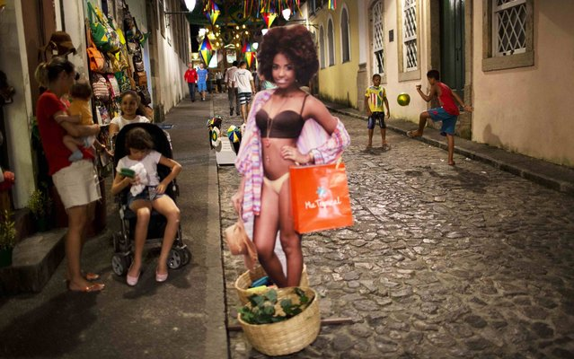 A life-size image of a woman promoting a shop stands in the street where children play soccer in the Pelourinho neighborhood of Salvador, Brazil, Monday, June 30, 2014. Salvador is one of many cities hosting World Cup soccer games. (Photo by Rodrigo Abd/AP Photo)
