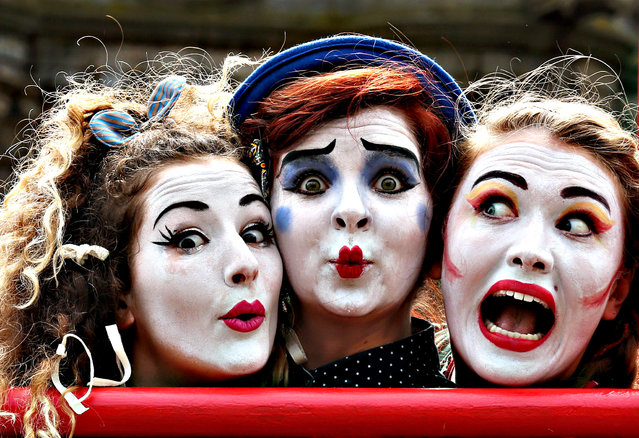 """Performers (left to right) Fleur Tooth, Florence O'Mahony and Rosalind Hoy from the Human Zoo Theatre Company, on the Royal Mile in Edinburgh, advertise their act """"The Girl Who Fell In love With The Moon"""" which is on at the  Pleasance Dome, ahead of the Edinburgh Fringe Festival which starts tomorrow and lasts till the 31st of August. (Photo by Andrew Milligan/PA Wire)"""