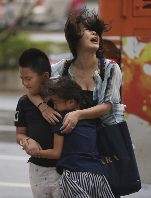 A mother holds her children in strong gusts from Typhoon Soudelor in Taipei, Taiwan, Friday, August 8, 2015. (Photo by Wally Santana/AP Photo)