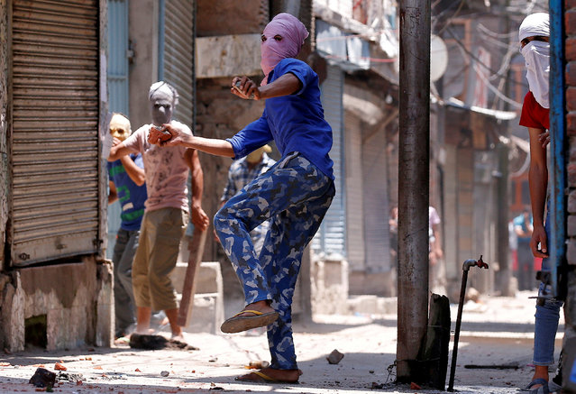 A masked protetser throws pieces of bricks and stones towards Indian police officers during a clash on the occassion of the death anniversary of Burhan Wani, a commander of the Hizbul Mujahideen militant group, in downtown Srinagar July 8, 2017. (Photo by Danish Ismail/Reuters)