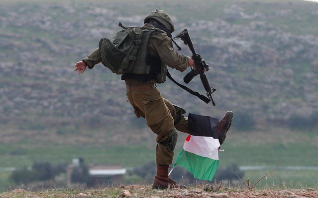 An Israeli soldier kicks a Palestinian flag during a protest against Trump's Middle East peace plan, in Jordan Valley in the Israeli-occupied West Bank on January 29, 2020. (Photo by Mohamad Torokman/Reuters)
