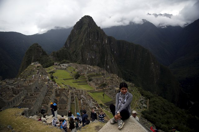 A tourist poses for a photo at the Inca citadel of Machu Picchu in Cusco, Peru, August 12, 2015. Machu Picchu, a UNESCO World Heritage Site, is Peru's top tourist attraction, with the government limiting tourists to 2,500 per day due to safety reasons and concerns over the preservation of the ruins. The Machu Picchu and Huayna Picchu mountains will be undergoing maintenance works, therefore suspending visitors from the areas, in the month of April 2016, according to Archaeological Park director Fernando Astete. (Photo by Pilar Olivares/Reuters)