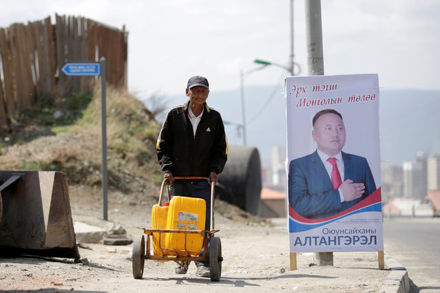 A villager carries water past a poster of an independent candidate for the upcoming parliamentary elections on the outskirts of Ulan Bator, Mongolia, June 27, 2016. (Photo by Jason Lee/Reuters)