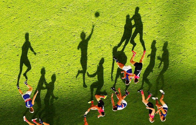 Long shadows are cast by players as Mitch Wallis of the Bulldogs passes the ball during the 2016 AFL Round 08 match between the Melbourne Demons and the Western Bulldogs at the Melbourne Cricket Ground, Melbourne on May 15, 2016. (Photo by Scott Barbour/AFL Media/Getty Images)