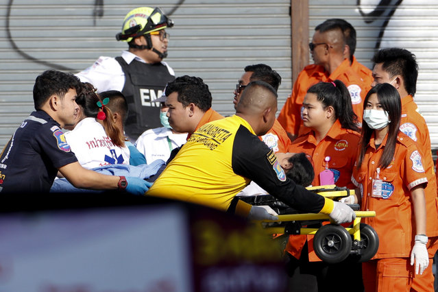 Medics transport a victim on a stretcher at the scene of a mass shooting at the Terminal 21 shopping mall in Nakhon Ratchasima, Thailand, 09 February 2020. (Photo by Rungroj Yongrit/EPA/EFE)