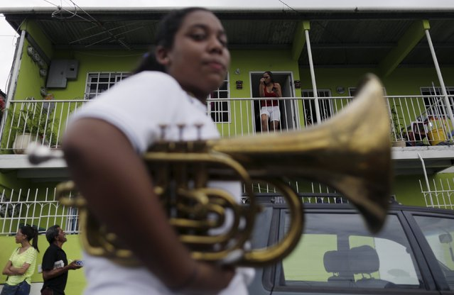 A resident looks at a parade marking the 496th anniversary of Panama City, Panama August 15, 2015. Modern-day Panama City includes the historical ruins of the original Panama Viejo settlement founded on August 15, 1519 by Spaniard Pedro Arias Davila, according to local media. (Photo by Carlos Jasso/Reuters)