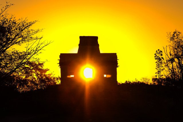 The sun shines directly through the door of the Seven Dolls Temple, in the Maya Ruins of Dzibilchaltun, in the Mexican state of Yucatan, as it rises on the spring equinox on March 20, 2017. (Photo by Elizabeth Ruiz/AFP Photo)