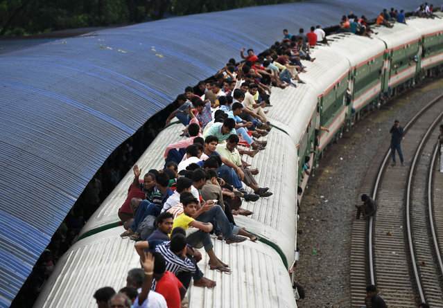 Passengers sit on the roof of an overcrowded train as they return home ahead of the Muslim holiday of Eid al-Fitr, at a railway station in Dhaka, Bangladesh, Friday, July 1, 2016. Hundreds of thousands of people working in Dhaka leave for their home towns every year to celebrate Eid al-Fitr with their family. (Photo by A.M. Ahad/AP Photo)
