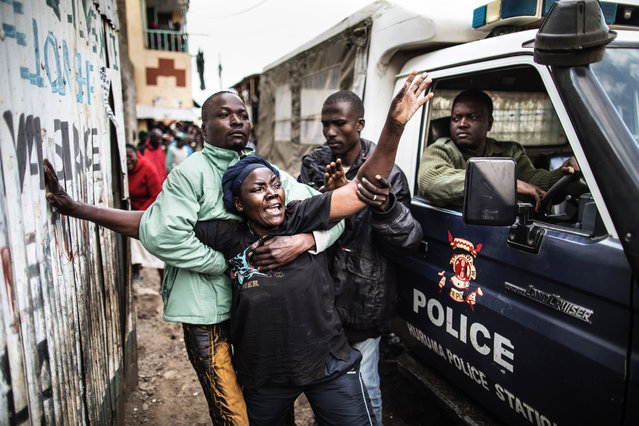 The mother of a man shot in the head allegedly by Kenyan police reacts as she passes a police van transporting her son's body in an alley  of Mathare slum in Nairobi, on August 9, 2017, as unrest broke out a day after general elections. (Photo by Marco Longari/AFP Photo)