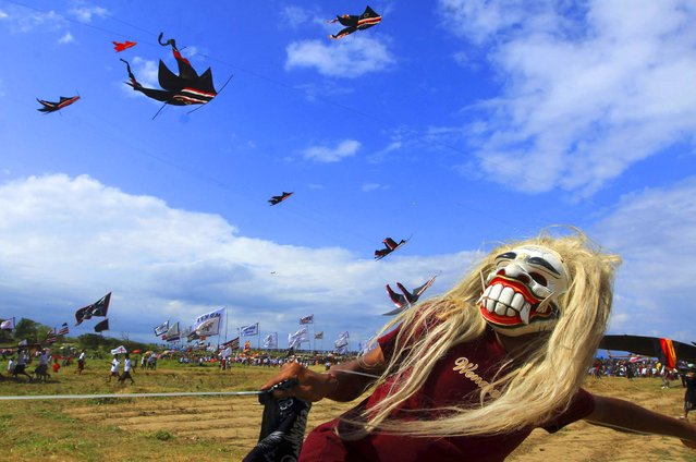 A boy wears a mask while flying a traditional kite during a kite festival on Padang Galak island of Bali, Indonesia