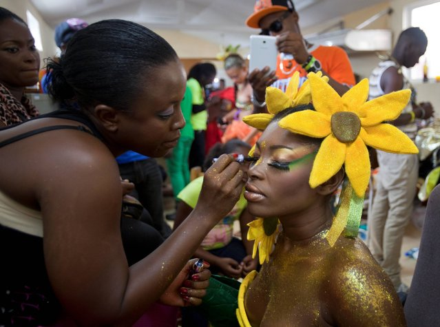 """A carnival queen gets her makeup done before the start of Carnaval des Fleurs, or Carnival of Flowers celebrations in Port-au-Prince, Haiti, Tuesday, July 29, 2014. The Caribbean nation is celebrating its third """"Carnival of Flowers"""", a three-day celebration President Michel Martelly has revived from the Duvalier era. (Photo by Dieu Nalio Chery/AP Photo)"""