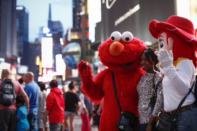 Jorge, an immigrant from Mexico, poses with a woman while dressed as the Sesame Street character Elmo in Times Square, New York July 29, 2014. (Photo by Eduardo Munoz/Reuters)