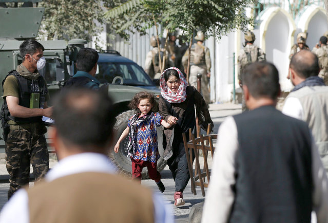 A woman and a child run after being rescued from the site of a suicide attack followed by a clash between Afghan forces and insurgents after an attack on a Shi'ite Muslim mosque in Kabul, Afghanistan on Friday, August 25, 2017. (Photo by Mohammad Ismail/Reuters)