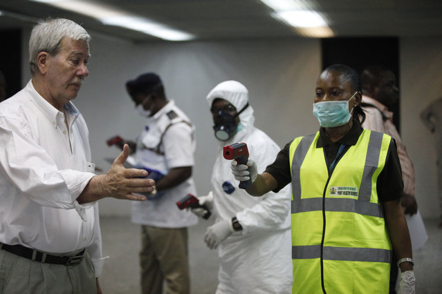 Nigerian port health officials uses a thermometer on a worker at the arrivals hall of Murtala Muhammed International Airport in Lagos, Nigeria, Wednesday, August 6, 2014. A Nigerian nurse who treated a man with Ebola is now dead and five others are sick with one of the world's most virulent diseases, authorities said Wednesday as the death toll rose to at least 932 people in four West African countries. (Photo by Sunday Alamba/AP Photo)