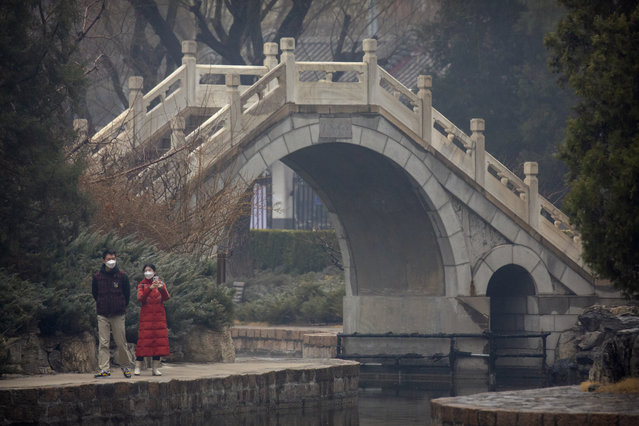 A couple wear face masks as they walk at a public park in Beijing, Saturday, February 29, 2020. (Photo by Mark Schiefelbein/AP Photo)
