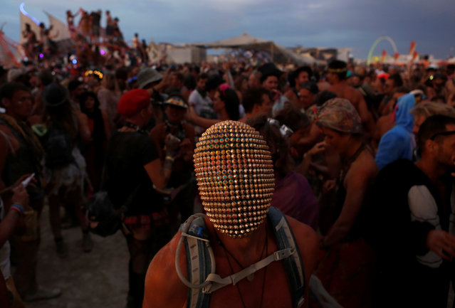 A participant wears a mask as he dances as approximately 70,000 people from all over the world gathered for the annual Burning Man arts and music festival in the Black Rock Desert of Nevada, U.S. August 29, 2017. (Photo by Jim Urquhart/Reuters)