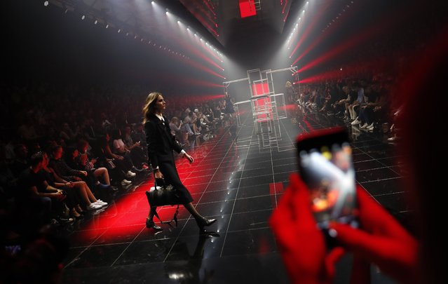 "A woman takes a picture of a model on the catwalk during the Hugo Boss show as part of the trade and fashion show ""Bread and Butter"", in Berlin, Germany, 02 September 2017. The lifestyle event, owned by online fashion retailer Zalando, includes international brands presenting their latest collections, interactive shows and everyday clothing stands. ""Bread and Butter"" is open for the general public and takes places from the 01 to 03 of September 2017. (Photo by Felipe Trueba/EPA/EFE)"