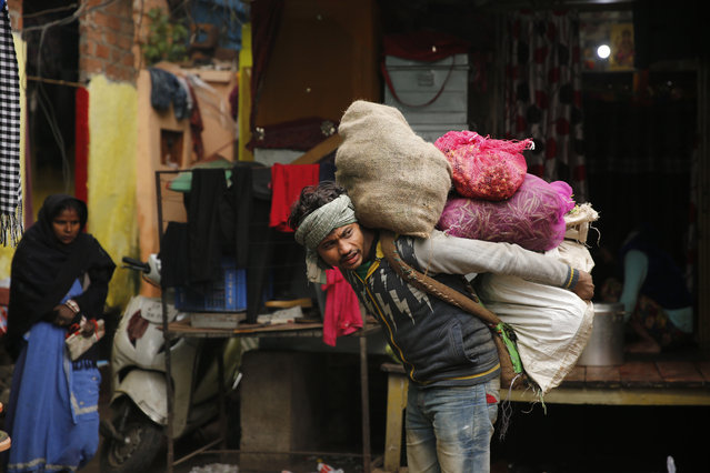 A worker carries vegetables on his back at a market in Lucknow, India, Sunday, December 29, 2019. (Photo by Rajesh Kumar Singh/AP Photo)