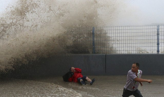 A visitor falls after trying to run away from a wave caused by a tidal bore which surged past a barrier on the banks of Qiantang River, in Hangzhou, Zhejiang province August 14, 2014. (Photo by Reuters/Stringer)