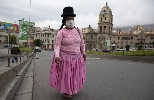 A woman walks in an empty street near the Basilica of San Francisco during a government ordered lockdown, which limits residents to shopping in the morning, as a measure to help contain the spread of the new coronavirus in La Paz, Bolivia, Tuesday, April 7, 2020. (Photo by Juan Karita/AP Photo)