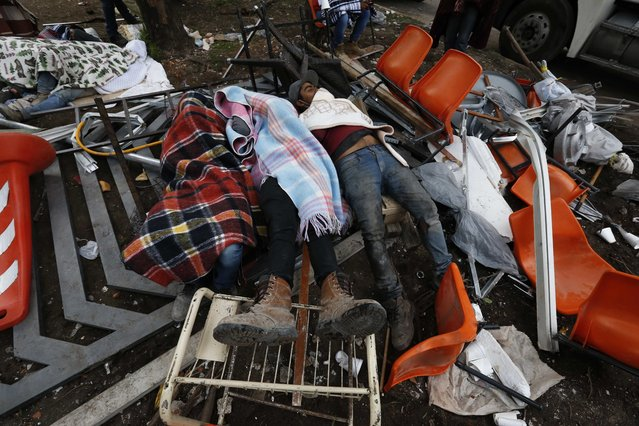 Rescue workers rest atop a toppled gate and amid debris as others continue the search and rescue efforts at the Enrique Rebsamen school that collapsed after an earthquake in Mexico City, Wednesday, September 20, 2017. One of the most desperate rescue efforts was at this school, where a wing of the three-story building collapsed into a massive pancake of concrete slabs. (Photo by Marco Ugarte/AP Photo)