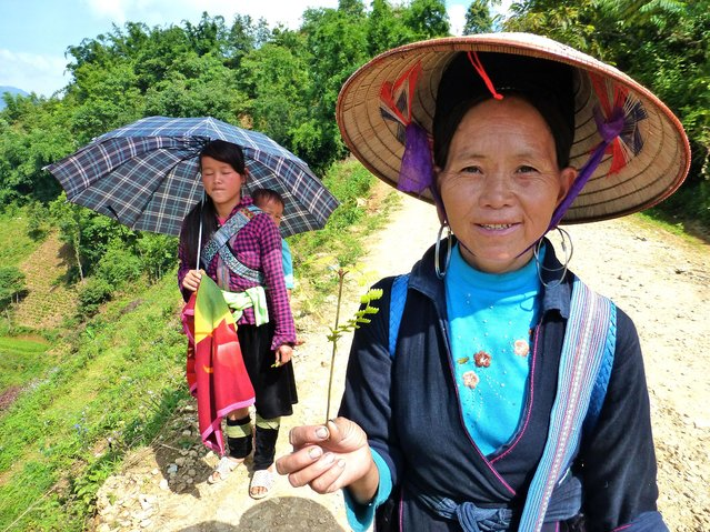 """""""These ladies (two, plus baby) are members of the Black H'mong ethnic group living in the hill country around Sapa, Vietnam"""", wrote Susan Sauer Sloan, 57, of Great Falls, Va. """"A large group of women voluntarily accompanied my husband and me along a winding trail, presenting us with gifts woven from grasses collected along the way. The woman in the foreground here has just made me a heart"""". (Photo by Susan Sauer Sloan)"""