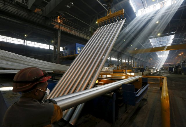 An employee works with cylindrical 6-metre aluminium ingots at the the Rusal Sayanogorsk aluminium smelter outside the town of Sayanogorsk, Russia, September 3, 2015. (Photo by Ilya Naymushin/Reuters)