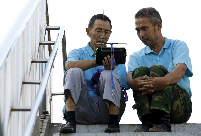 Security volunteers watch a video related to the parade near the Changan Avenue, ahead of the military parade to mark the 70th anniversary of the end of World War Two, in Beijing, China, September 3, 2015. (Photo by Kim Kyung-Hoon/Reuters)