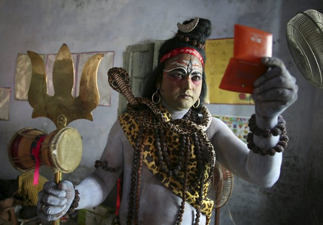 A man dressed as Hindu Lord Shiva looks into the mirror as he gets ready to take part in a religious procession on the eve of Janmashtami festival in Amritsar, India, September 4, 2015. The festival, which marks the birth anniversary of Lord Krishna, will be celebrated across India on Saturday. (Photo by Munish Sharma/Reuters)