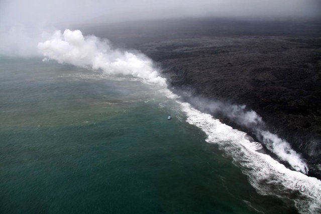 In this December 27, 2011 photo provided by the U.S. Geological Survey, Lava flows in to the ocean at West Ka'ili'ili in in Hawaii Volcanoes National Park. Hawaii County Civil Defense Acting Administrator John Drummond says the lava at Kilauea isn't threatening homes or structures but steam is blasting from the point where it reaches the sea along the coast. (Photo by AP Photo/U.S. Geological Survey)