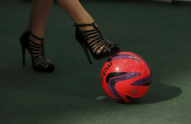 A woman wearing high heeled shoes kicks a football as she tries out Foot Golf at the Soccerex convention in Manchester, northern Britain, September 7, 2015. (Photo by Phil Noble/Reuters)
