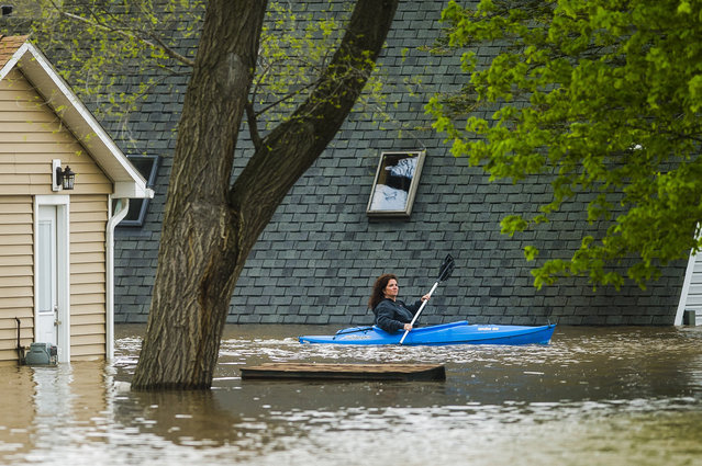 People use kayaks to assess the damage at homes in their neighborhood on Oakridge Road on Wixom Lake, Tuesday, May 19, 2020 in Beaverton, Mich. (Photo by Katy Kildee/Midland Daily News via AP Photo)