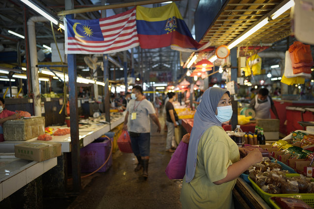 A woman wearing a face mask to help stop the spread of the coronavirus shops at a wet market in downtown Kuala Lumpur, Malaysia, Friday, April 24, 2020. (Photo by Vincent Thian/AP Photo)