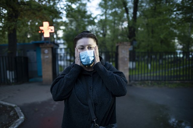 In this photo taken on Monday, May 18, 2020, Dr. Irina Vaskyanina adjusts a face mask to protect against coronavirus during her interview with the Associated Press in front of a hospital in Reutov, just outside Moscow, Russia. Vaskyanina headed a department handling blood transfusions at a hospital in Reutov, outside Moscow, and spent weeks fighting for better working conditions after 40 of her colleagues got infected with the virus and dozens quit. (Photo by Alexander Zemlianichenko/AP Photo)