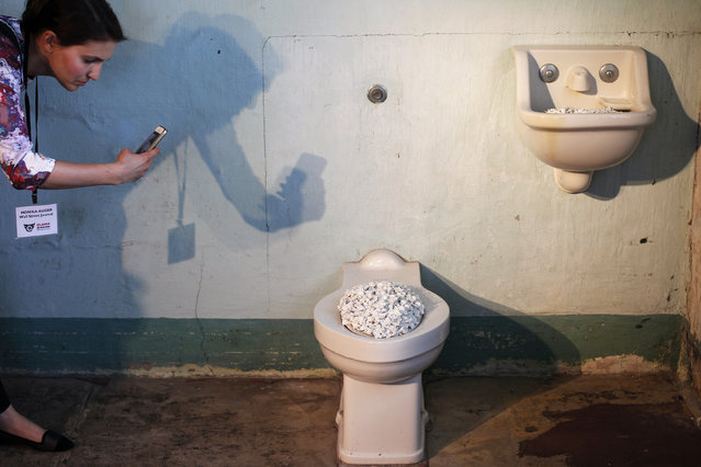 """A members of the media uses a mobile phone to take pictures of Ai Weiwei's installation """"Blossom"""" in the hospital ward of Golden Gate National Recreation Area's Alcatraz Island near San Francisco, California, September 24, 2014. """"Blossom"""" consists of toilets, sinks and baths filled with ceramic flowers. (Photo by Beck Diefenbach/Reuters)"""