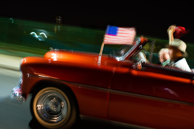 A European tourist throws his arm into the air as the historic car he hired bearing an American flag, drives down the historic Malecon on the evening of January 31, 2015. (Photo by Sarah L. Voisin/The Washington Post)