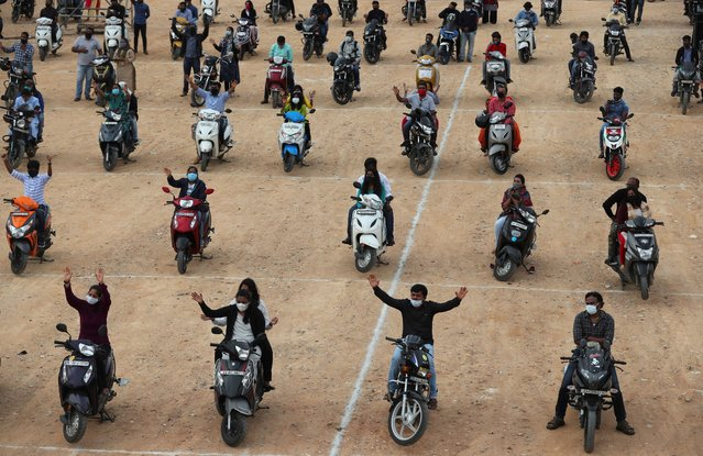 Faithful sit on their two-wheelers and pray as they attend a drive-in mass in an open area of Bethel AG Church as part of maintaining social distancing to prevent the spread of coronavirus in Bengaluru, India, Sunday, June 21, 2020. India is the fourth hardest-hit country by the COVID-19 pandemic in the world after the U.S., Russia and Brazil. (Photo by Aijaz Rahi/AP Photo)