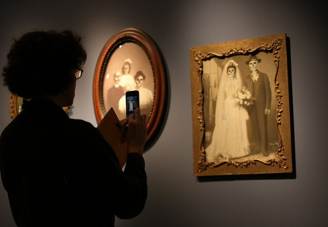 """A visitor photographs a work by Mexican artist Marcos Raya called Family Portrait : Wedding  at the """"Death: A Self-portrait"""" exhibition at the Wellcome Collection on November 14, 2012 in London, England. The exhibition showcases 300 works from a unique collection by Richard Harris, a former antique print dealer from Chicago, devoted to the iconography of death. The display highlights art works, historical artifacts, anatomical illustrations and ephemera from around the world and opens on November 15, 2012 until February 24, 2013.  (Photo by Peter Macdiarmid)"""