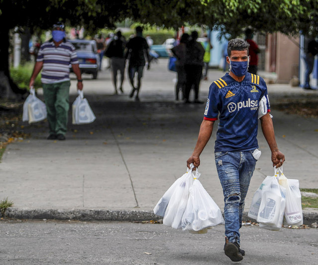 People with masks walk as they carry shopping bags, in Havana, Cuba, 19 May 2020. Cuba continues this Tuesday the downward trend in daily infections of COVID-19, with only six new cases on its sixth consecutive day without deaths, according to the daily part of the Ministry of Public Health (Minsap). (Photo by Yander Zamora/EPA/EFE/Rex Features/Shutterstock)