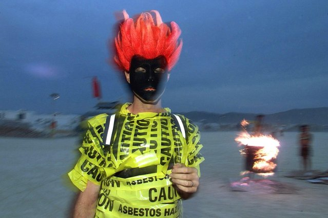 A masked man walks near a fire in Black Rock City during the Burning Man Festival in Nevada, 30 August 2000. An estimated 30,000 people will attend the festival – a spontaneous encounter of artists, performers and spectators – where the audience is expected to interact and collaborate during the week-long event. (Photo by Hector/AFP Photo)