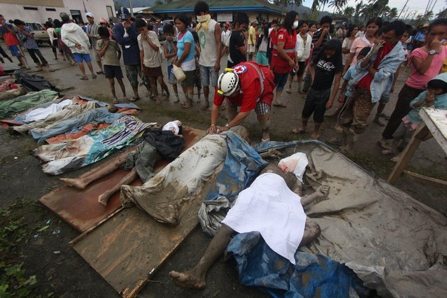 A rescuer covers bodies recovered from flashflood in New Bataan, Compostela Valley province, southern Philippines Wednesday, December 5, 2012. The death toll from Typhoon Bhopa climbed to more than 100 people Wednesday, while scores of others remain missing in the worst-hit areas of the southern Philippines. (Photo by Karlos Manlupig/AP Photo)
