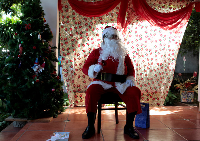 A man dressed as Santa Claus waits to have his photo taken with children at a primary school in Managua, Nicaragua on December 20, 2017. (Photo by Oswaldo Rivas/Reuters)