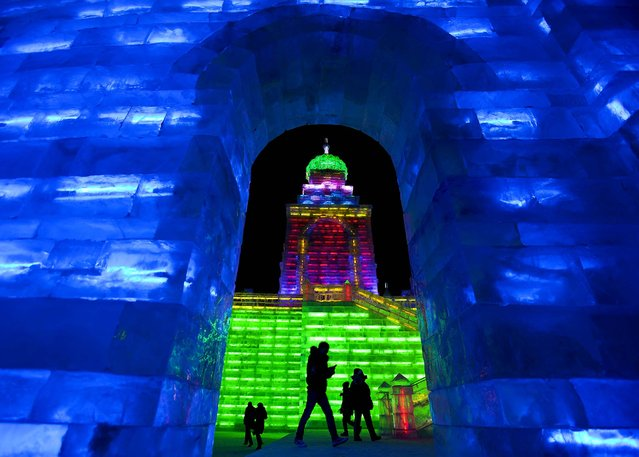 Visitors view buildings made from blocks of ice for the Harbin International Ice and Snow Festival on Wednesday, January 4, 2012. (Photo by Andy Wong/Associated Press)