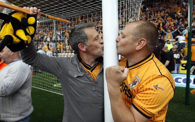 Wolverhampton Wanderer fans kiss the goal post after their English Premier League soccer match against Blackburn Rovers at the Molineux stadium in Wolverhampton, May 22, 2011. Wolves avoided relegation despite coming from 3-0 down to lose 3-2 to Blackburn, a defeat that was celebrated as if they had won the league and also secured Blackburn's safety. (Photo by Andrew Winning/Reuters)